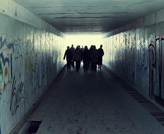 Gang walking in tunnel with grafiti